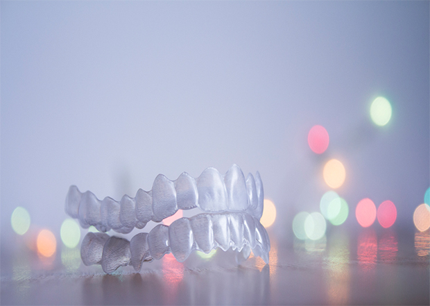 A set of upper and lower clear aligners against a background of colored lights - Alternatives to braces