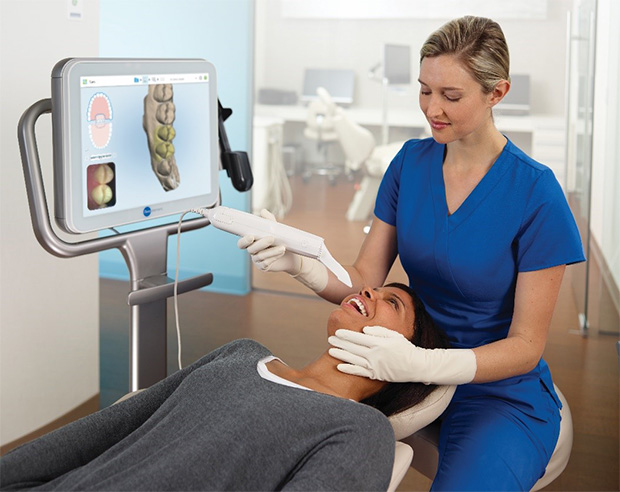 A dental technician uses the iTero® impressionless dental scanner on a smiling patient.