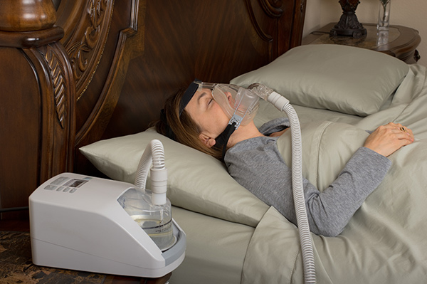 Woman sleeping in bed with a mask attached to a CPAP device.