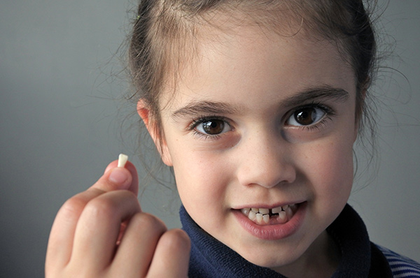 Young girl smiling while holding her missing tooth in her hand.