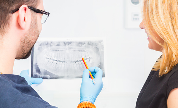 Dentist discussing a dental x-ray with his patient.