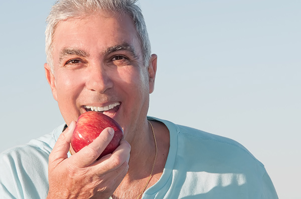 Smiling senior man holding an apple.
