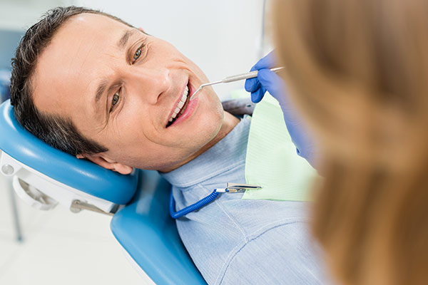 A man having his teeth cleaned at the dentist.
