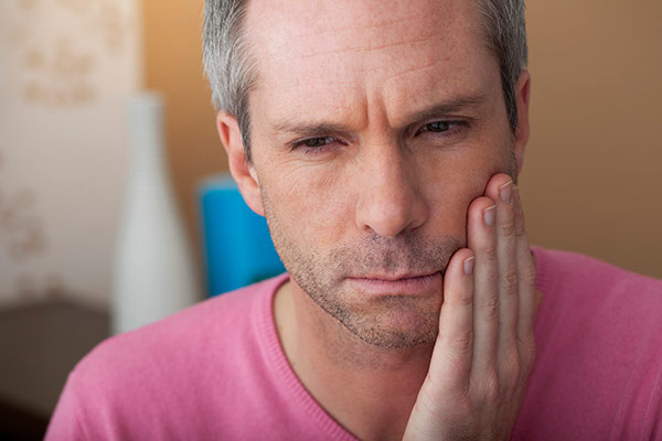 A man that needs tooth abscess treatment holding his jaw.