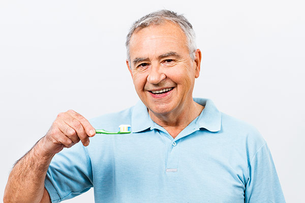 A man with gray hair smiles as he prepares to brush his aging teeth.