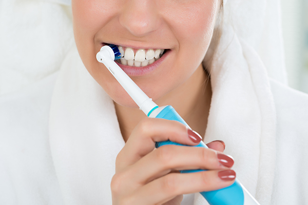 A woman with an electric toothbrush