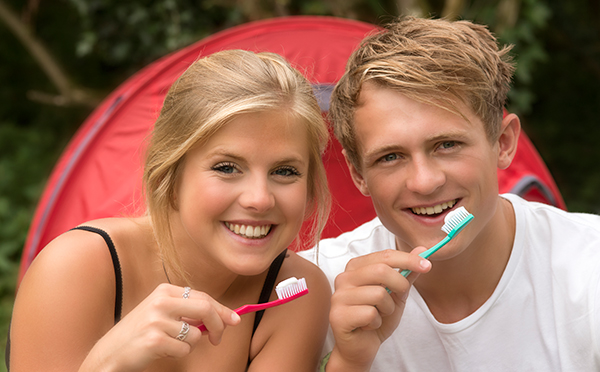 Two people camping with manual toothbrushes