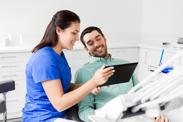 Dental hygienist with patient discussing periodontal disease treatment options.