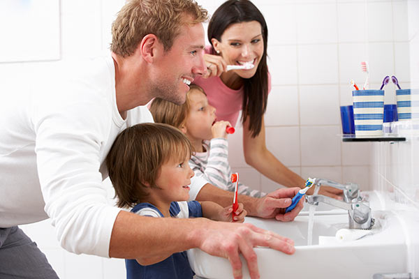 Parents teaching their children how to brush their teeth.