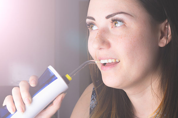 A woman using a water flosser