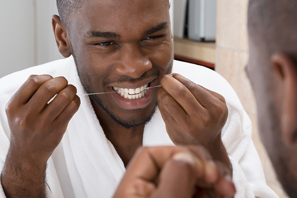 A man cleaning his teeth using dental floss