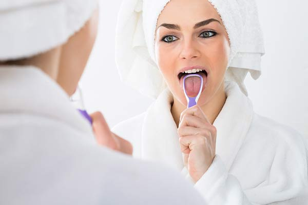 A woman learning how to clean her tongue with a tongue scraper.