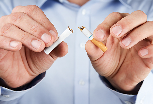 A smoker breaking his cigarette due to the effects of smoking on oral health