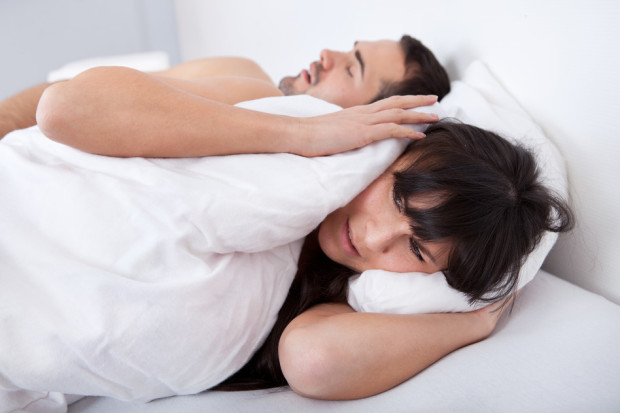 Woman covers her ears with a pillow and blanket while man snores next to her.