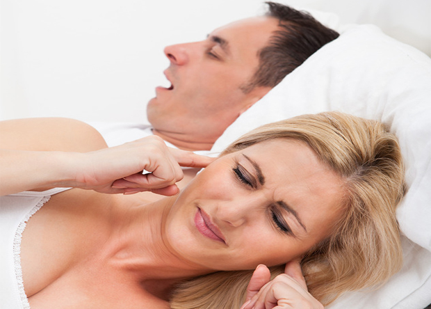 Woman in bed plugs her ears as man snores next to her
