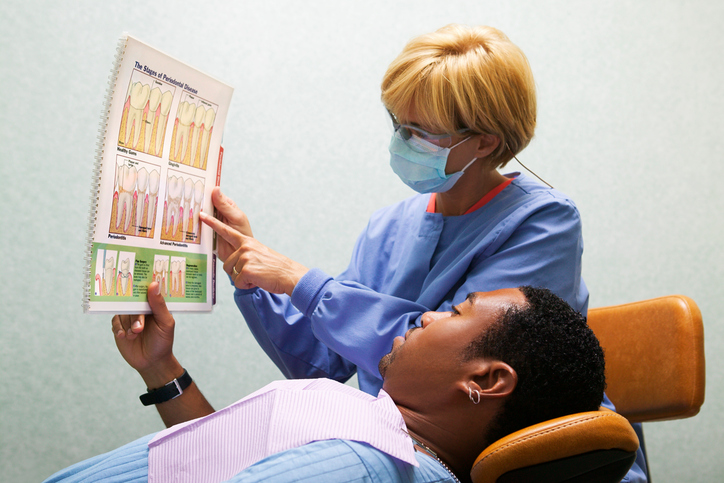 Dental hygienist shows a chart explaining periodontal disease to a patient.
