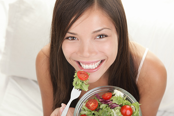 Best Food for Healthy Gums & Teeth | Happy woman smiling while eating a healthy salad with tomatoes.