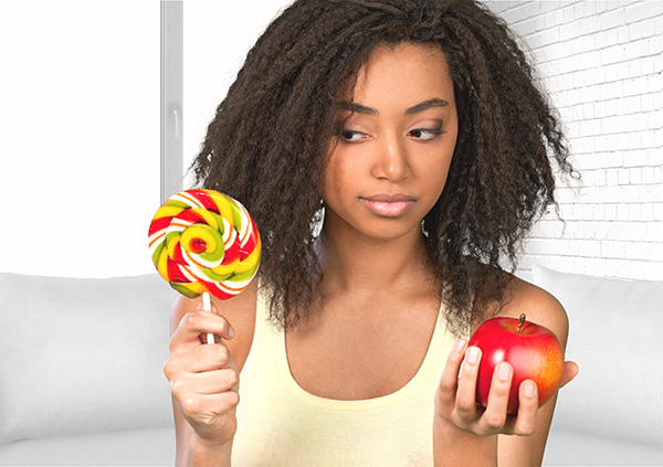 Why it's hard to avoid eating sugar - Woman holding an apple and large lollypop in her hands.