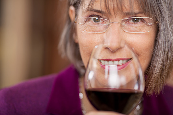 Woman smiling with white teeth behind glass of red wine.