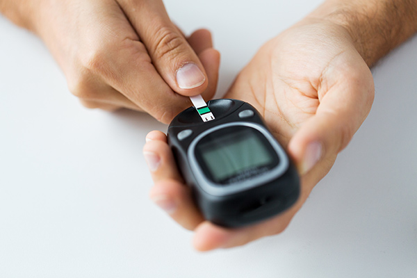 Man testing blood sugar levels with a glucometer and test strip.