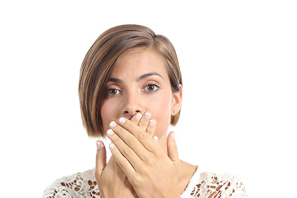 Woman with bad breath covering her mouth.