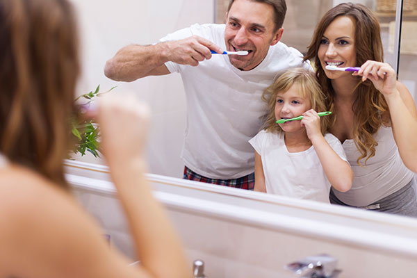 Family of three brushing their teeth together in the mirror.